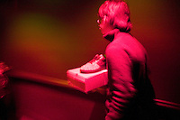 A man carries a pair of sneakers atop their box hoping to attract a buyer during Dunkxchange, a market held in a club in New York City, USA, where sneaker collectors trade and sell their rare shoes, 7 January 2007.<br />