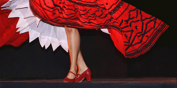 The bright red skirt, trimmed with black design, is worn by a female dancer preforming Jalsico, one of the traditional dances presented by the Ballet Folklorico de Mexico in which female dancers wear colorful costumes that swirl with the movement of the dance. The dancer's white petticoat, legs and red shoes are seen all against a black background.
