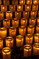 Candles lit as offerings at the Notre Dame Cathedral in Paris, France.