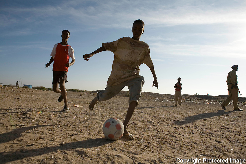 Bujo Baley camp, North Galkayo, Somalia..Children of school age play football in the morning light.. there are few opportunities for kids to go to school so many either work, play or do nothing.