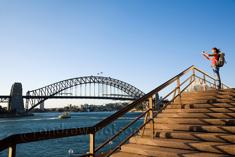 A backpacker photographs the Sydney Harbour Bridge from the steps of the Opera House at sunset.  Sydney, New South Wales, AUSTRALIA.