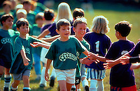 Youth soccer players in traditional post-game handshake line.