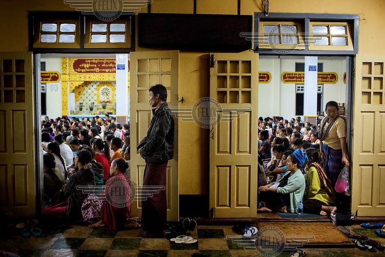 Followers of U Wirathu, the spiritual leader of the radical Buddhist 969 movement, watch him deliver a sermon on a projector screen in an overflow area of the Thein Taung Monastery in Taunggyi, Shan State. /Felix Features