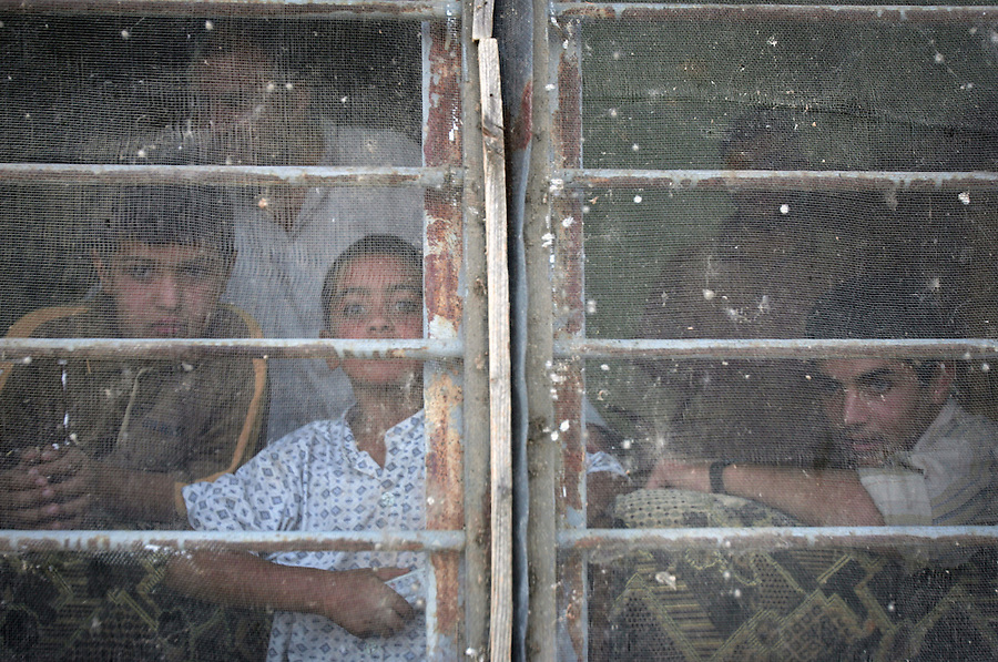 An Iraqi family watches a passing US Marine patrol from behind a screened window as two days ahead of the Oct. 15th vote, Marines from Kilo Co. 3rd Battalion, 1st Marines (3/1) flier and pass out handbills and copies of the proposed Iraqi constitution to residents of Haditha, Iraq in Al-Anbar Province on Thursday, Oct. 13, 2005. The push to distribute information to voters comes in the context of the on-going Operation Rivergate in the city, which continues to uncover scores of IEDs, weapons caches, and suspected insurgents.