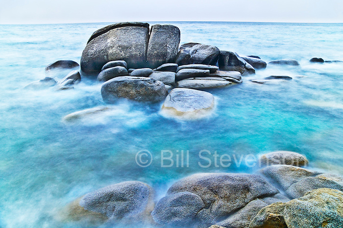 An abstract landscape photo of rocks and blurred water along the east shore of Lake Tahoe. In an effort to make something different than the millions of other images of Lake Tahoe I went out on a stormy day. The blurred water is the the result of a one minute exposure while the waves rolled in over the rocks.