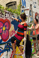 Spray painting the word freedom on the mural.