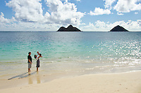 A father looking on while a mother lifts their son on Lanikai Beach, O'ahu, with the Mokulua Islands in the distance.