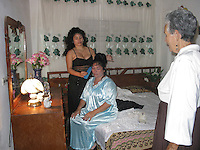 Feb 12 2003, Holguin, CUBA <br /> A Teenager (L) and a grandmother (R) help  the bride on a Cuban civil wedding in Holguin,<br /> Photo (c) 2004) P Roussel / Images Distribution