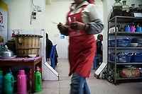 A waitress carries food in a small restaurant in Xinjie, Yuanyang County, Yunnan Province, China.