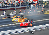 Feb 13, 2016; Pomona, CA, USA; NHRA funny car driver Jim Campbell (far) explodes an engine on fire alongside Gary Densham during the Winternationals at Auto Club Raceway at Pomona. Mandatory Credit: Mark J. Rebilas-USA TODAY Sports