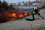 A Palestinian protester burns tires during clashes with Israeli troops following a demonstration near the Jewish settlement of Beit El, near Ramallah, in the occupied West Bank June 29, 2018. Photo by Shadi Hatem