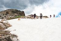 Backpackers traverse a snowfield near Upper Aero Lake in the Absaroka-Beartooth Wilderness.