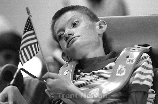 Boy with American flag at talent show for mentally disabled children.<br />