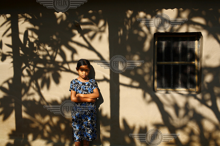 A Garo girl stands among the shadows from a tree. The Garo (or Mandi, as they refer to themselves) are an ethnic minority thought to be of Tibeto-Burmese origin. Prior to British rule they were mostly anamists but missionary work led the majority to convert to Christianity. The Garo of the Madhupur forest have long been under the threat of eviction by the government and the forest that they gain much of their livelihood from is being rapidly destroyed by unregulated logging.