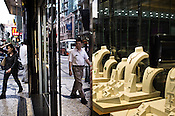 Pedestrians walk past a shop displaying the gold and jade jewelry on their shop window in Central Macau, China.