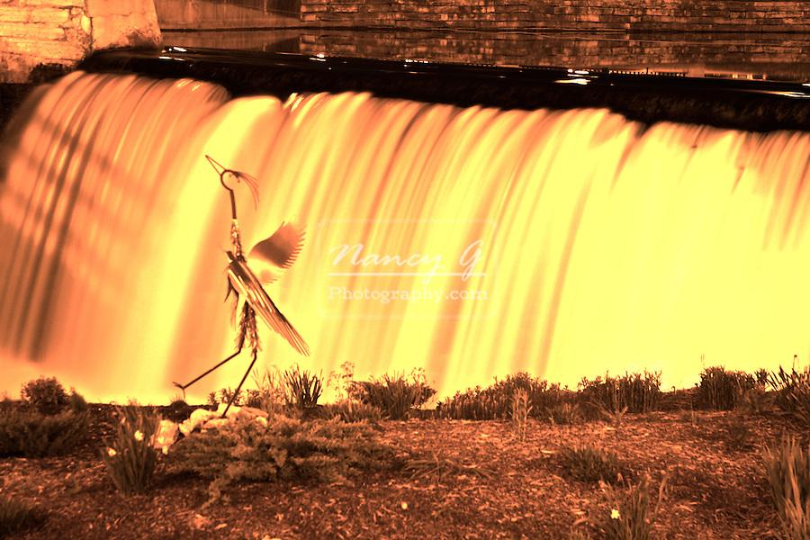 Blue Herring Crane statue in front of a dam waterfall in Menomonee Falls Wisconsin