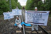 """Klimacamp """"Ende Gelaende"""" bei Elsterheide in der brandenburgischen Lausitz.<br /> Mehrere tausend Klimaaktivisten  aus Europa wollen zwischen dem 13. Mai und dem 16. Mai 2016 mit Aktionen den Braunkohletagebau blockieren um gegen die Nutzung fossiler Energie zu protestieren.<br /> Im Bild: Klimaaktivsten aus Schweden, Oesterreich, Finnland, und Deutschland bereiten sich darauf vor die Schienen einer Kohletransportstrecke zu blockieren. Sie haben eine Vorrichtung zum anketten unter den Schienen befestigt. Hinter ihnen der letzte Kohlezug, der auf dieser Strecke das Kraftwerk Schwarze Pumpe an diesem Tag erreicht.<br /> 13.5.2016, Elsterheide/Brandenburg<br /> Copyright: Christian-Ditsch.de<br /> [Inhaltsveraendernde Manipulation des Fotos nur nach ausdruecklicher Genehmigung des Fotografen. Vereinbarungen ueber Abtretung von Persoenlichkeitsrechten/Model Release der abgebildeten Person/Personen liegen nicht vor. NO MODEL RELEASE! Nur fuer Redaktionelle Zwecke. Don't publish without copyright Christian-Ditsch.de, Veroeffentlichung nur mit Fotografennennung, sowie gegen Honorar, MwSt. und Beleg. Konto: I N G - D i B a, IBAN DE58500105175400192269, BIC INGDDEFFXXX, Kontakt: post@christian-ditsch.de<br /> Bei der Bearbeitung der Dateiinformationen darf die Urheberkennzeichnung in den EXIF- und  IPTC-Daten nicht entfernt werden, diese sind in digitalen Medien nach §95c UrhG rechtlich geschuetzt. Der Urhebervermerk wird gemaess §13 UrhG verlangt.]"""