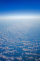 Aerial view of scattered clouds over ocean water with horizon and blue sky