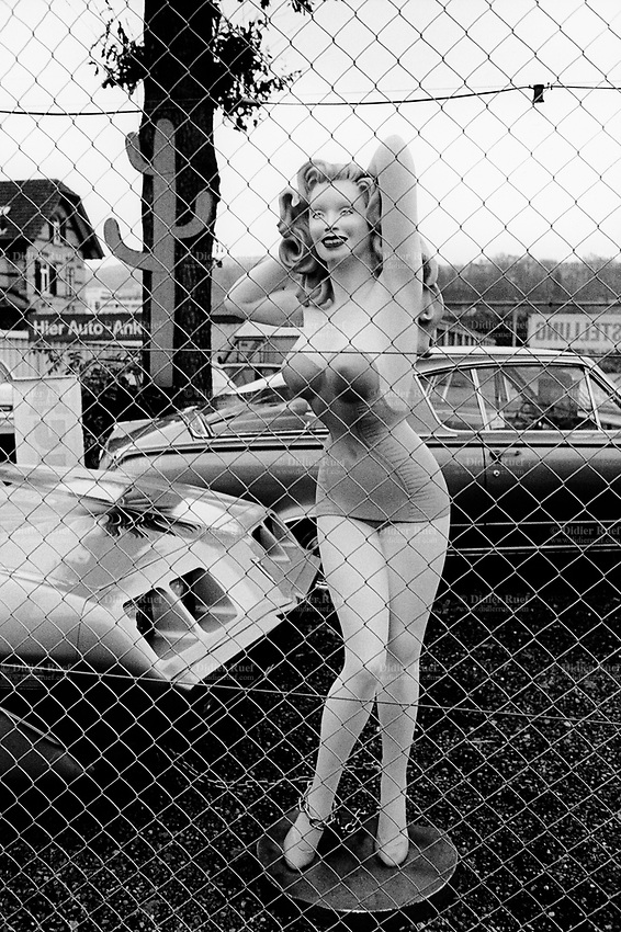 "Switzerland. Zürich. Car showroom. A giant plastic pin-up dummy, wearing a mini skirt and a sexy top, stands in a yard of a sale shop for secondhand american cars. A smiling Marylyn Monroe and a fake cactus. Marilyn Monroe (born Norma Jeane Mortenson; June 1, 1926 – August 5, 1962) was an American actress, model, and singer. Famous for playing comic ""blonde bombshell"" characters, she became one of the most popular sex symbols of the 1950s and was emblematic of the era's attitudes towards sexuality. © 1999 Didier Ruef"
