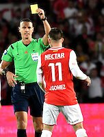 BOGOTA - COLOMBIA - 18-12-2016: Wilmar Roldan, referee, shows yellow cadr to Jonatan Gomez (R) player of Independiente Santa Fe, during a match for the second leg between Independiente Santa Fe and Deportes Tolima, for the final of the Liga Aguila II -2016 at the Nemesio Camacho El Campin Stadium in Bogota city, Photo: VizzorImage / Luis Ramirez / Staff.