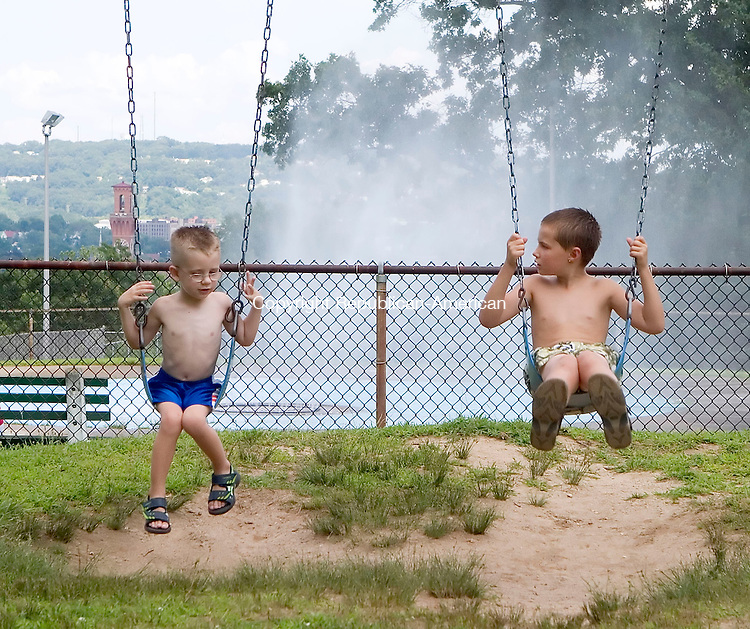 WATERBURY, CT- 30 JULY 06- 073006JT13-<br /> Cousins Jacob Thompson, 4, and Dayne Fasske, 9, chat as they swing with a sprinkler behind them at Chase Park on Sunday afternoon.<br /> Josalee Thrift Republican-American