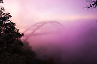 Fog covers the 360 Bridge during sunrise on a cold winter's morning on Lake Austin, Texas.