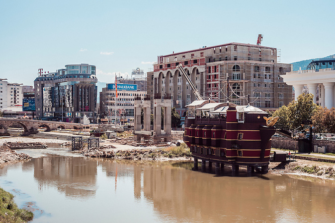 Vardar Ufer, ein Boot (evtl ein Restaurant) steht auf Pfosten im Fluss<br />