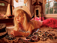 A little blonde girl lays on her bedroom floor playing dress up with her mom's jewelry