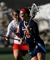 Gabi Wiegand (9) of Richmond tries to find a way past Elizabeth Hamilton (22) of Maryland at the practice turf field in College Park, Maryland.  Maryland defeated Richmond, 17-7.