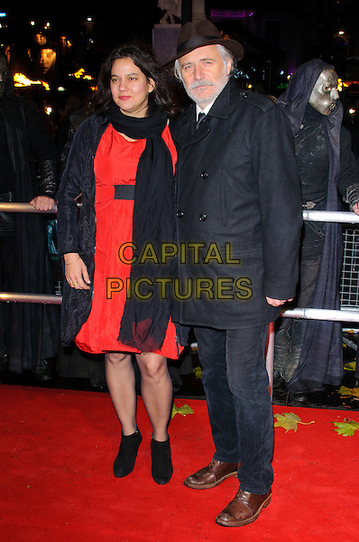 "GUEST & RADE  SERBEDZIJA  .""Harry Potter And The Deathly Hallows: Part 1"" World Film Premiere, Empire cinema Leicester Square and Odeon Leicester Square, London, England, UK, .11th November 2010..full length red dress black hat coat blue trousers brown shoes scarf .CAP/CJ.©Chris Joseph/Capital Pictures."