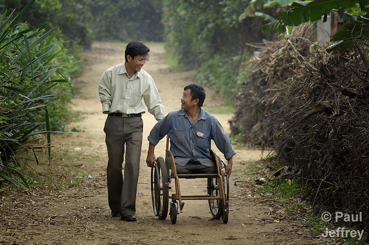 Tran Van Son (right) is a carpenter in Bo Trach, Vietnam, who lost his legs to a landmine from the U.S. war against Vietnam. Here he travels along a path near his home with Hoang Van Luu, who lost an arm to a landmine.
