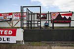 A solitary away fan reading his programme surrounded by flags and banners inside Key's Park prior to the Hednesford Town versus FC United of Manchester Northern premier League Premier division play-off final. The match would decide which club were promoted to the Blue Square Conference North. Hednesford won the game by 2 goals to 1 in front of a stadium record attendance of 4412 spectators.