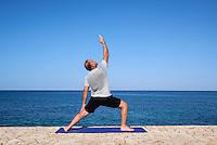 Man practices morning yoaga at a seaside spa.