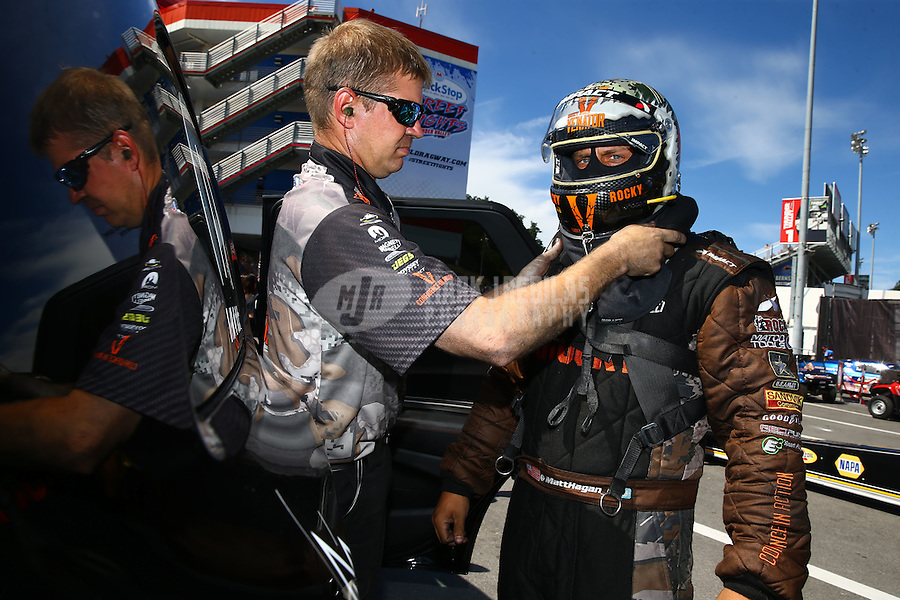 Jun 19, 2016; Bristol, TN, USA; Crew member helps NHRA funny car driver Matt Hagan with safety gear during the Thunder Valley Nationals at Bristol Dragway. Mandatory Credit: Mark J. Rebilas-USA TODAY Sports