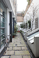 The entrance to the converted studio is down a gravel pathway punctuated with large floating paving stones