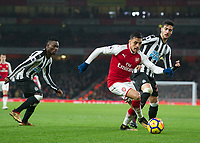 Alexis Sanchez of Arsenal gets away from Christian Atsu of Newcastle United and Mikel Merino of Newcastle United during the Premier League match between Arsenal and Newcastle United at the Emirates Stadium, London, England on 16 December 2017. Photo by Vince  Mignott / PRiME Media Images.