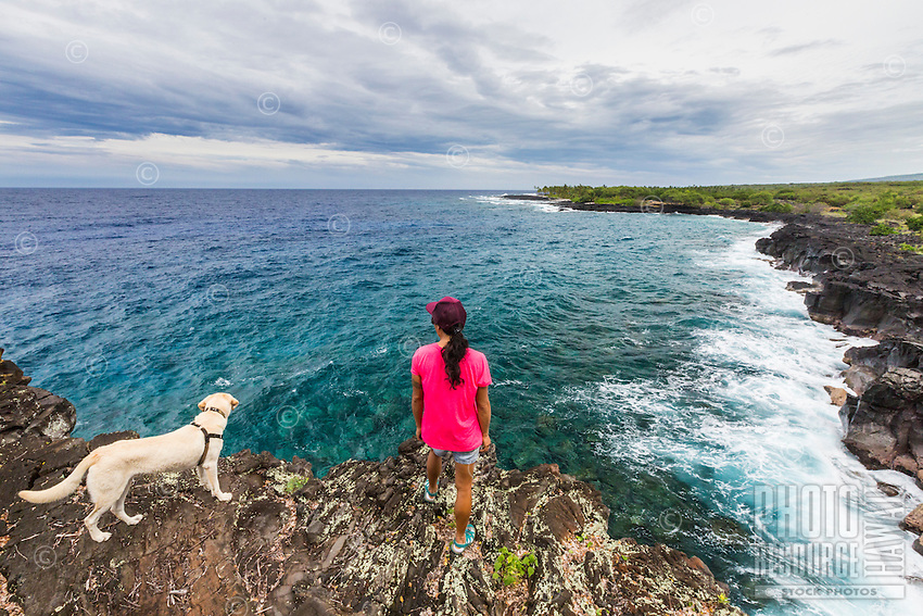 A woman and her dog hiking the historic 1871 Trail pause to take in the view in Honanau, Big Island. The ancient trail was the main artery for coastal travel between several villages in the area.
