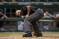 Umpire Jose Navas cleans off home plate during the International League game between the Scranton/Wilkes-Barre RailRiders and the Charlotte Knights at BB&T BallPark on August 14, 2019 in Charlotte, North Carolina. The Knights defeated the RailRiders 13-12 in ten innings. (Brian Westerholt/Four Seam Images)