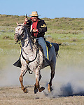 A calvary soldier drawing his weapon on horseback in full gallop at the 134th Annual Battle of the Little Bighorn Reenactment located in Hardin Montana. 8x10 format. Model release.