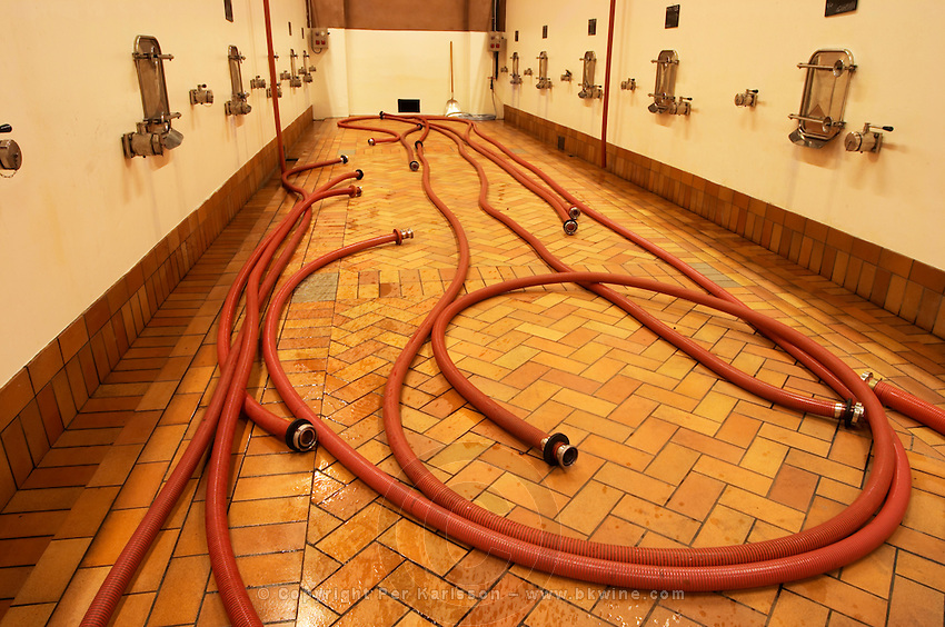 The winery with large concrete fermentation vats and a pipes for pumping wine on the floor. Chateau de Beaucastel, Domaines Perrin, Courthézon Courthezon Vaucluse France Europe