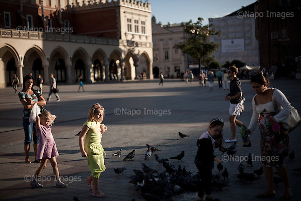 KRAKOW, POLAND, SEPTEMBER 13, 2011:.Children and their mothers are feeding pigeons in the evening at the Old Town's main square.(Photo by Piotr Malecki / Napo Images) ..KRAKOW, 9/2011:.Stary Rynek..Fot: Piotr Malecki / Napo Images