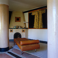 A tan Mies Van der Rohe Barcelona daybed stands between two columns and the wall of the room is decorated with an ornately embroidered coat