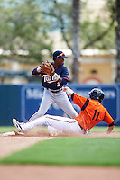 GCL Twins shortstop Gorge Munoz (2) throws to first as Glynn Davis (11) slides into second base during a game against the GCL Orioles on August 11, 2016 at the Ed Smith Stadium in Sarasota, Florida.  GCL Twins defeated GCL Orioles 4-3.  (Mike Janes/Four Seam Images)