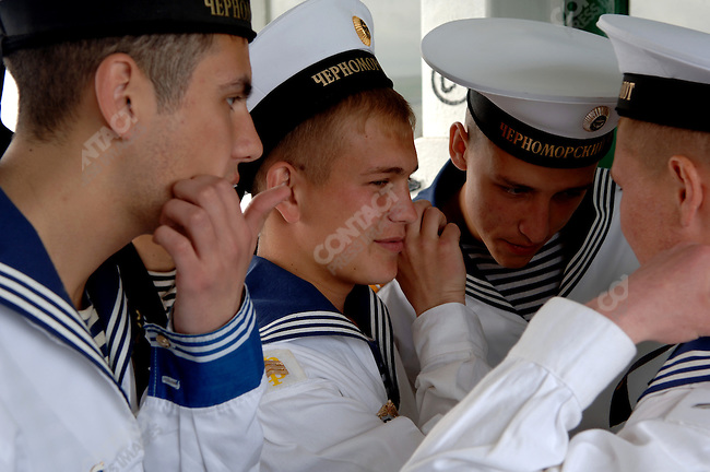 Sailors from the Black Sea Fleet listen to a cellphone while on crossing the harbor to Sevastopol. Republic of Crimea, May 28, 2006.