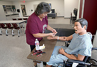 NWA Democrat-Gazette/DAVID GOTTSCHALK   Kay Milsap, of Gentry, examines Tuesday, August 8, 2017, a seated medical patient mannequin in one of the new classrooms inside the new Gentry Career and Technical Education Center on the high school campus. Guests, dignitaries and school personnel attended opening ceremonies at the center designed for the Bentonville, Decatur, Gentry and the Gravette School Districts. The center will concentrate on diesel technology and medical field professions.