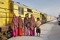 Young Indian women posing in front of Palace on Wheels train parked at train station, Udaipur, India.