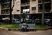 Un anziano signore siede in una panchina nella periferia della città
