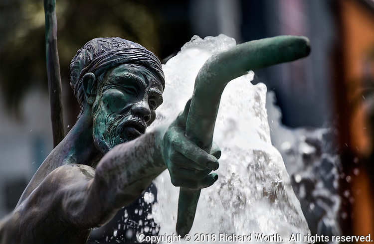 Close-up of the head of an Australian aboriginal fisherman, his extended hand holding a booerang, part of a statue in a water fountain outside a medical office building in Fremont, California.