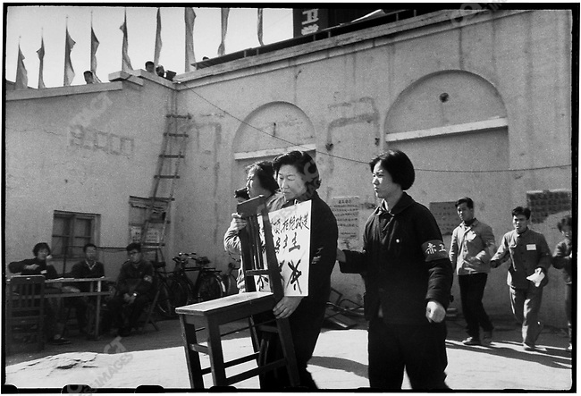 "Yu Ziwen, accused of being a ""big property owner"", is forced to carry a chair onto the stage at Red Guard Square and to stand on it for public criticism. The placard around her neck bears her mane and her crime. Harbin, 19 September 1966"