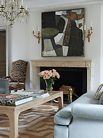 In the elegant family sitting room, the custom-made sofas covered in pale blue Donghia mohair flank a Chinese elm cocktail table from Mecox. A painting by Santiago Castillo hangs above an 18th-century French limestone fireplace, the stools are by Maison Jansen, the crystal chandelier is 19th-century and the abaca rug is by Patterson Flynn Martin.